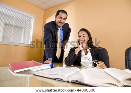 Young African-American female office worker with middle-aged Hispanic colleague in boardroom - stock photo
