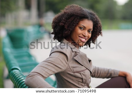 Young African American female sitting and smiling - stock photo