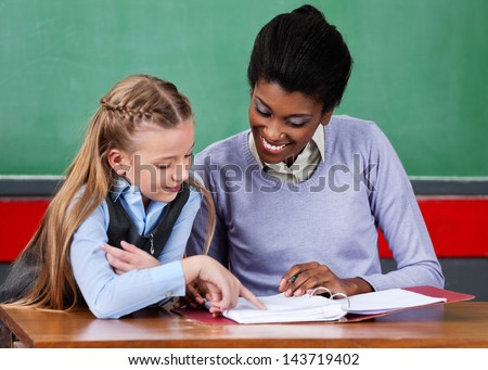 Young African American female teacher assisting schoolgirl at desk in classroom - stock photo
