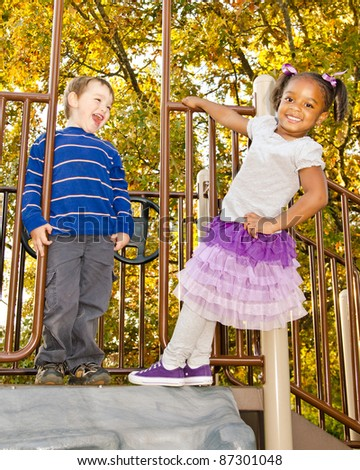 Young African-American girl and young white boy playing together in park - stock photo