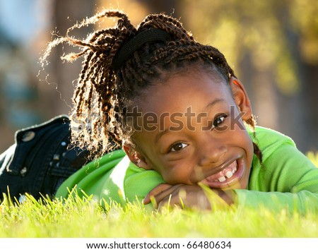 Young African American girl enjoying nice sunny day in a park. - stock photo