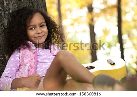 Young african american girl with afro singing and playing guitar outside in summer - stock photo