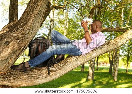 Young  african american lying on a tree branch in a park  and listens to music