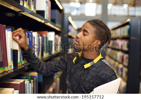 Young african american man finding books in public library. Finding information for his studies. - stock photo