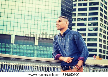 Young African American Man Grown in Big City. Wearing blue shirt, bracelets, a black college student standing in business district with high buildings, hoping, wishing, confidently looking forward. - stock photo