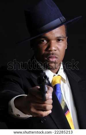 young African American man in a hat, suit and tie, pointing a revolver at the camera - stock photo