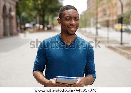 Young African American man in city walking using tablet pc