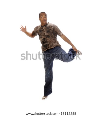young African American man leaping in the air holding his foot with a smile on his face - stock photo