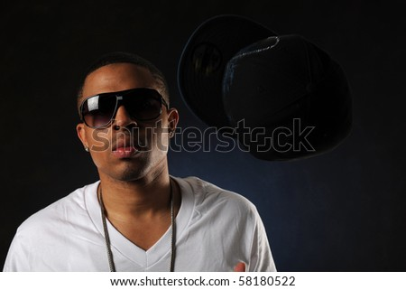 Young African American man's portrait wearing sunglasses against a dark background