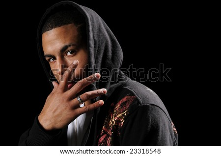 Young African American man with hood and hand in front of face - stock photo