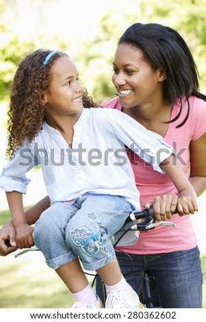 Young African American Mother And Daughter Cycling In Park - stock photo