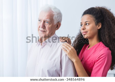 Young African American nurse supporting elder man
