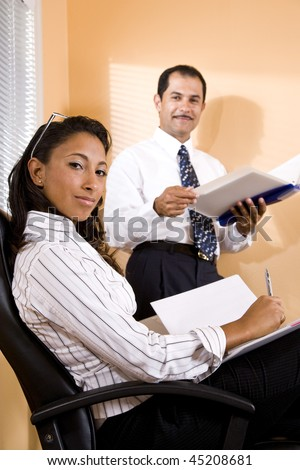 Young African-American office worker with middle-aged Hispanic co-worker in boardroom reviewing report - stock photo