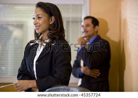 Young African-American office worker with middle-aged Hispanic manager in background - stock photo