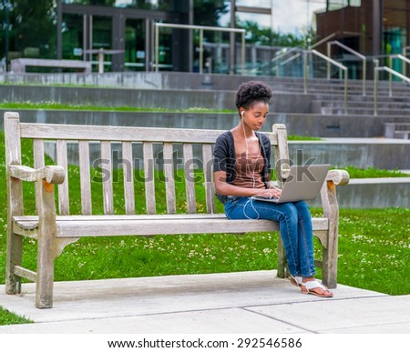 Young African American student sitting on bench doing homework while listening to music - stock photo