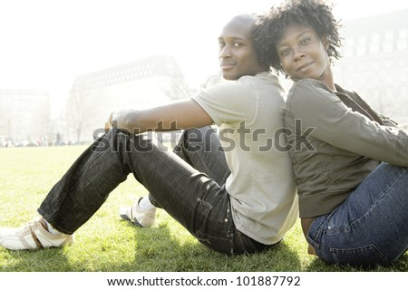 Young african american tourists sitting back to back on green grass in London city.