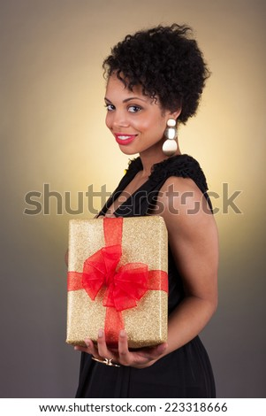 Young African American woman holding a gift box - stock photo