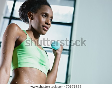 young african american woman in green sportswear doing weight lifting in fitness club. Horizontal shape, side view, copy space