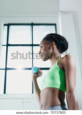 young african american woman in green sportswear doing weight lifting in fitness club. Vertical shape, side view, copy space