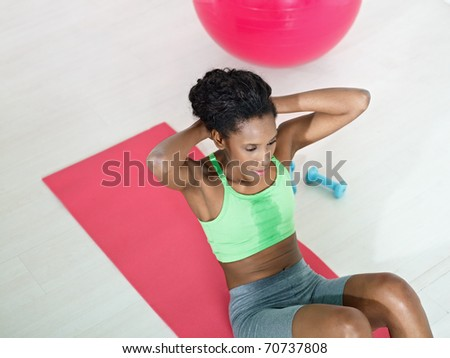 young african american woman in green sportswear exercising abdominals on pad in gym. Horizontal shape, high angle view, copy space