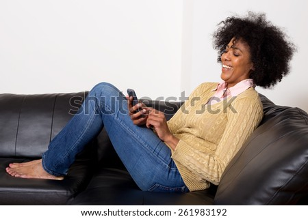 young african american woman reading her text messages at home - stock photo