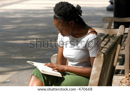 Young african american woman reads on a park bench. - stock photo