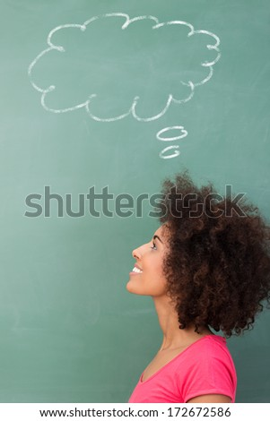 Young African American woman seeking inspiration standing looking up into the air with a smile below a thought bubble drawn on a green blackboard - stock photo