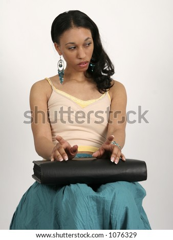 Young African American woman sitting impatiently with portfolio in her lap - stock photo