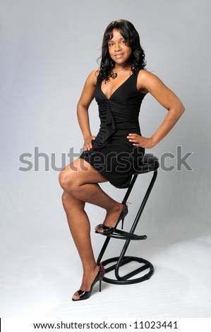 Young African American woman sitting on stool - stock photo