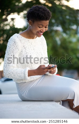 Young african american woman sitting outdoors sending text message with cellphone - stock photo