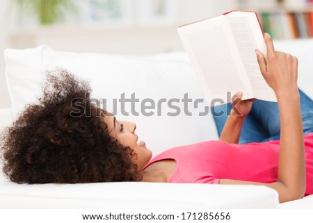 Young African American woman smiling while laying comfortably on her back on the sofa, reading a book - stock photo