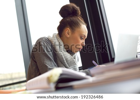 Young african american woman taking notes from books for her study. Sitting at table with books and laptop for finding information. - stock photo