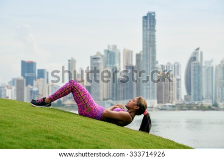 Young african american woman training abdominals and exercising early morning in the city. She trains on grass along the Cinta Costera in Panama City. Long shot - stock photo