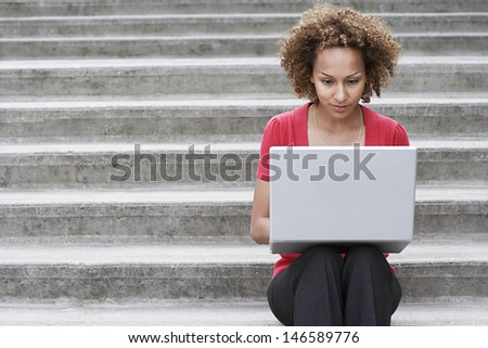 Young African American woman using laptop on steps outdoors - stock photo