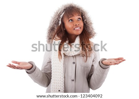 Young african american woman wearing winter clothes holding something in her hand, isolated on white background - stock photo