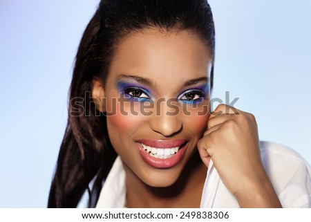 Young African American woman with colorful makeup. - stock photo