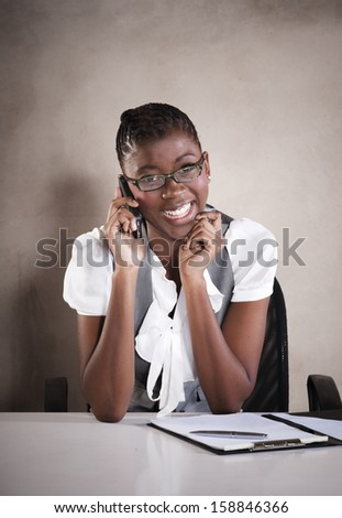 Young african business woman having a happy conversation on mobile phone