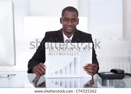 Young African Businessman At Desk In Office Showing Newspaper - stock photo
