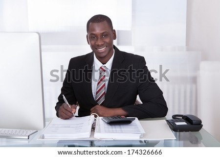 Young African Businessman Calculating Finance Bills With Calculator - stock photo
