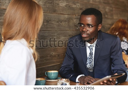 Young African businessman holding tablet and sharing data with female Caucasian colleague during coffee break in cosy café. Smart coworker makes an eye-contact with job partner and listens to her. - stock photo