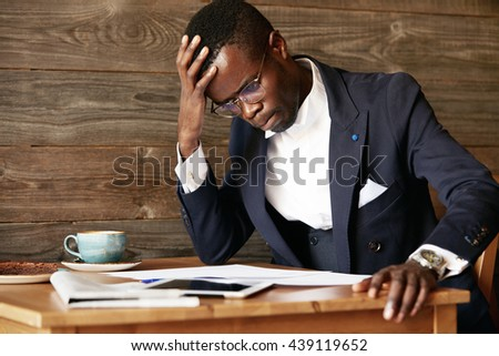 Young African businessman looking puzzled, having a computer problem, sitting in deep thinking pose, touching his forehead, squeezing lips and looking at papers, resting his elbow on the table - stock photo