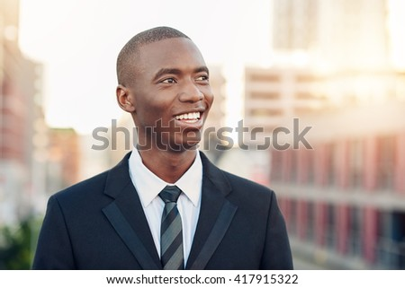 Young African businessman smiling while looking away optimistical