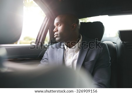 Young african businessman traveling to work in the luxury car on the back seat looking outside the window.