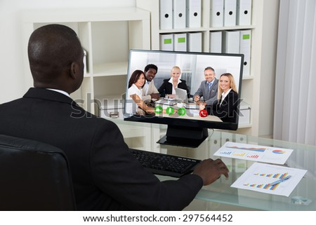 Young African Businessman Video Chatting With Colleagues On Computer In Office - stock photo