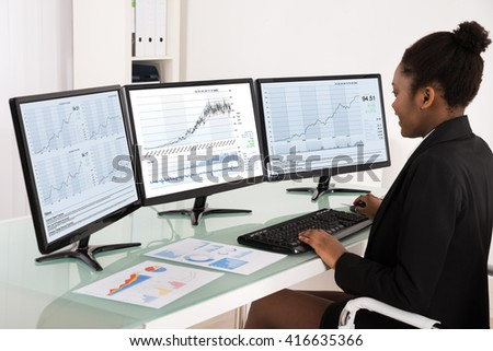 Young African Businesswoman Analyzing Data On Multiple Computer Screen In Office - stock photo