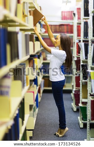 young african college student reaching for a book in library - stock photo