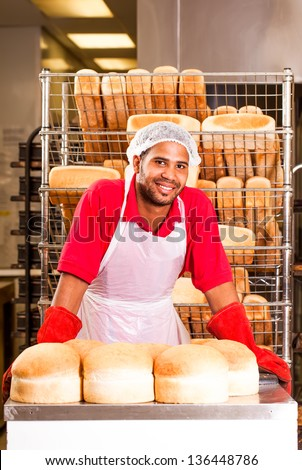 young african colored baker standing confidently behind a counter with round bread loaves - stock photo