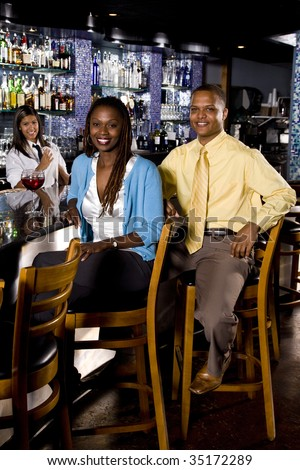Young African couple sitting at a bar - stock photo