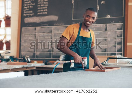 Young African craftsman working in a picture framing workshop - stock photo