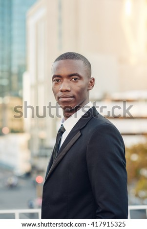 Young African finance entrepreneur in a city, looking serious